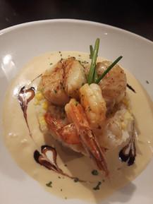 Scallops and shrimp atop sweet corn riso