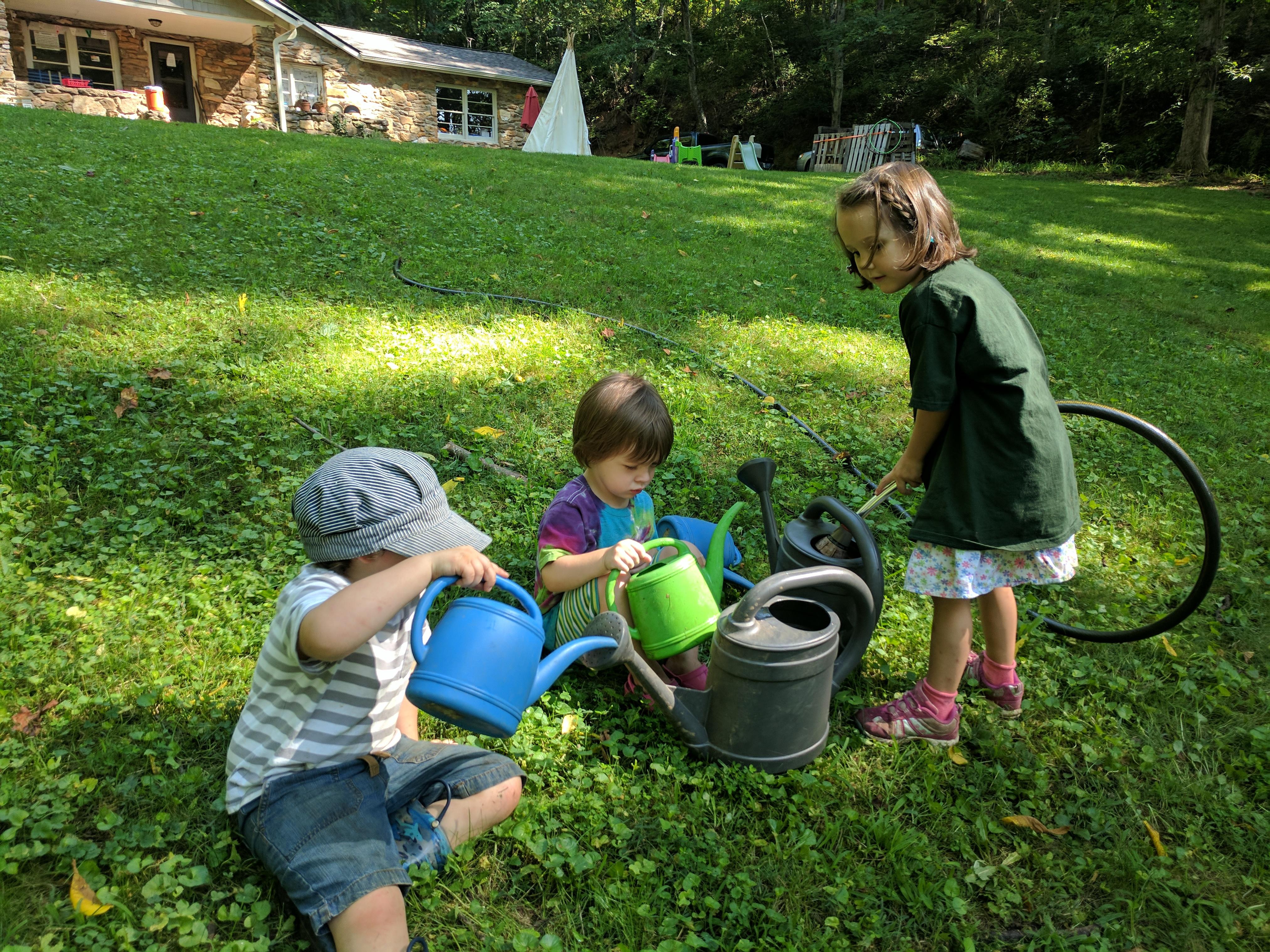 Asheville-farmstead-garden-watering-kids