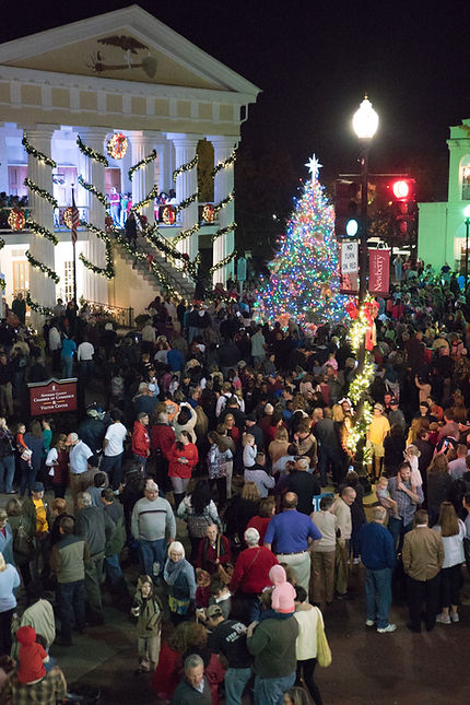 A large crowd during the Community Christmas tree lighting at a decorated Community Hall, gathered around the large 20+ foot Christmas tree decorated in thousands of colorful lights!
