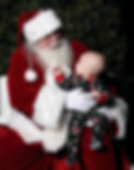 Santa and baby pose for a Christmas photo.