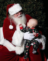 Santa and baby pose for a Christmas photo.