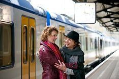 Friends hugging at a train station