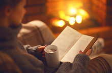 book and cup of coffee in hands of girl