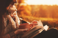 Beautiful girl in autumn forest reading