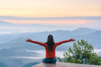 Happy traveler on mountain summit hands