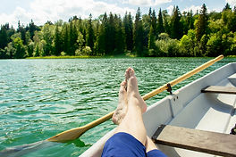 A man resting in a boat in the middle of