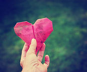 a hand holding an origami heart over gr