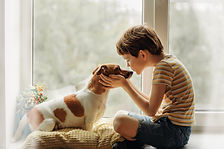 Little boy kisses the dog in nose on the