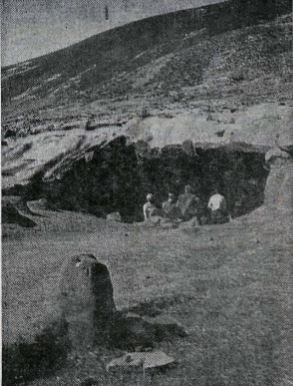 A black and white photo of four men sitting at the mouth of the Laugarvatnhellir caves in South Iceland.