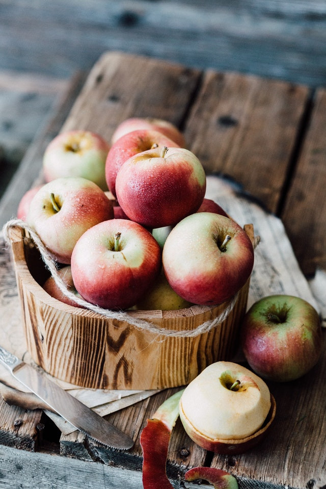 Wooden basket with twine handle filled with medium size apples. The basket is sitting on a wooden table. There is a butter knife and a half peeled apple resting on the table in front of the basket.