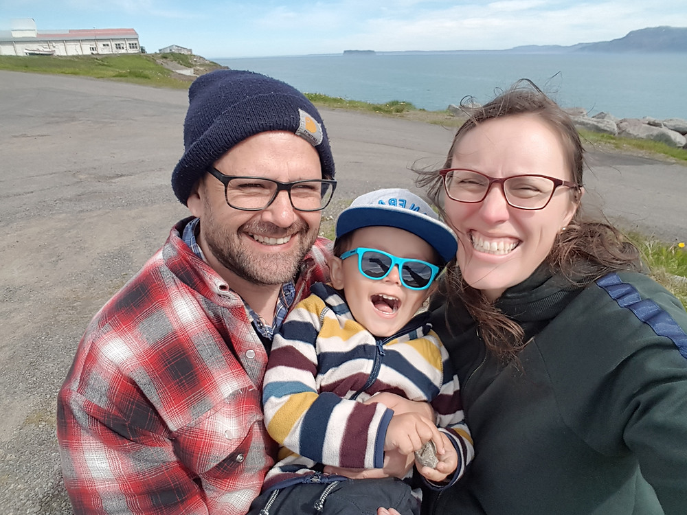 A photo Natalie and her husband and son in Hofsós, Iceland, posing on a sunny day with the island Drangey in the background.