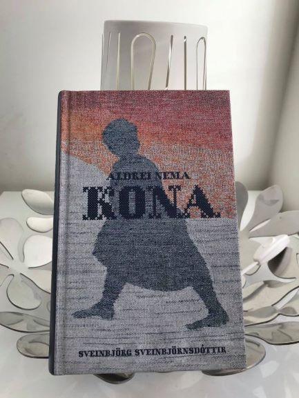 "Picture of Sveinbjörg Sveinbjörnsdóttir's book ""Aldrei nema kona"". The silhouette of a woman with a sunset background. The image looks like knitted fabric."