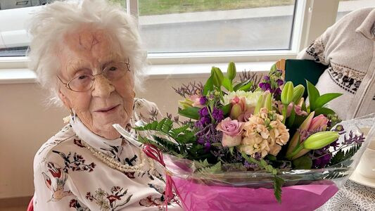 Photo of Helga on her birthday with bouquet of flowers