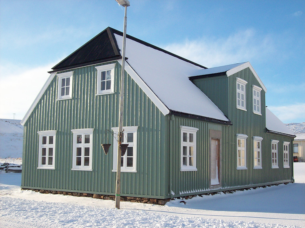 A picture of Riishús on a sunny, snowy day. The wooden walls have been painted green, the window trim is white, and the roof is black. Riishús is located in Borðeyri and Icelandic Roots gave a grant towards its restoration in 2020. #historiciceland #icelandhistory #bordeyri #riishus #icelandicrootsgrants #icelandicroots