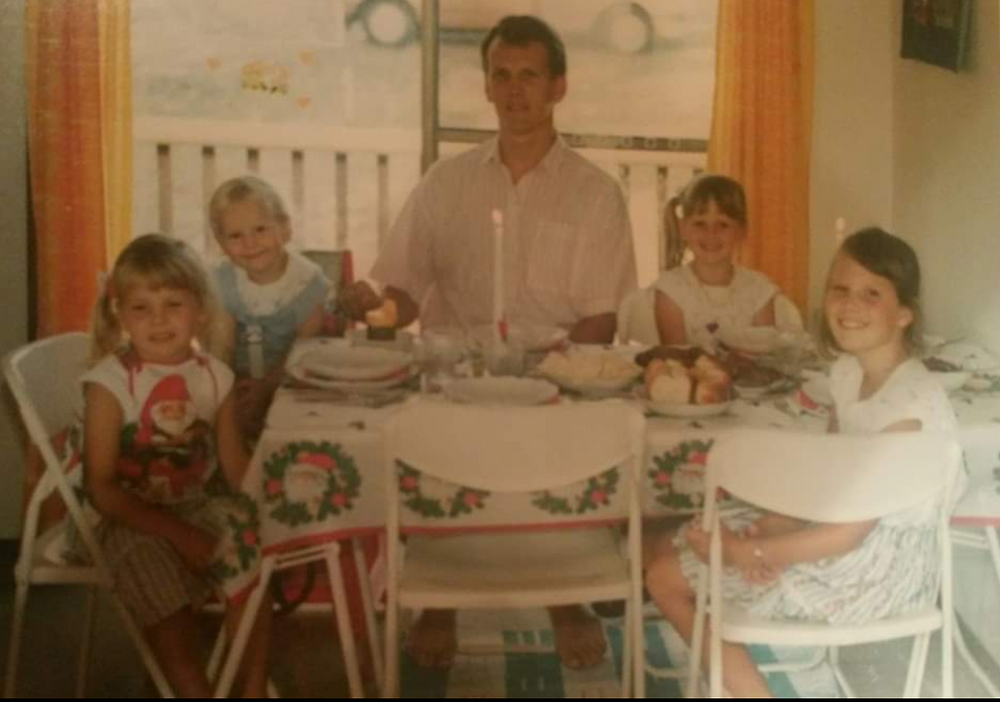 Elin's family sitting at a table set for Christmas dinner. Her father sits in the middle while two sisters sit on either side of him. Everyone is wearing short sleeves because it is summertime in Australia.
