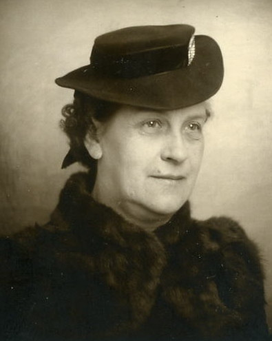 Portrait of Amma Stina wearing  a fur collar and black brimmed hat.