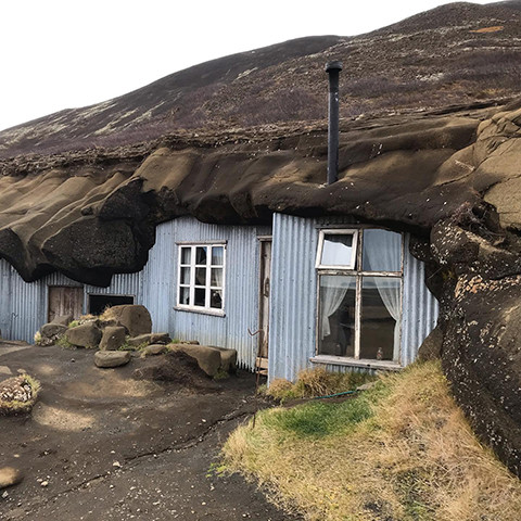 A photo of the Laugarvatnhellir cave in 2020. The caves now have a pale blue metal siding, along with glass windows, doors, and a chimney. Visitors can tour the inside of the cave-turned-home.