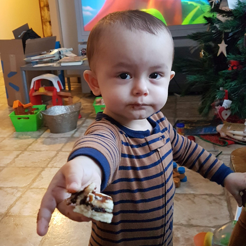 toddler looking at the camera, arm extended handing a piece of vinarterta to the camera