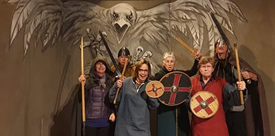 Snorri Plus group dressed as vikings in front of a raven mural.