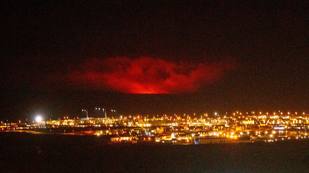 red reflection from iceland volcano, cityscape is Grindavik