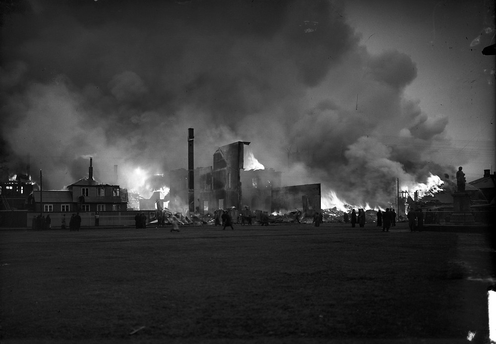 black and white photo of several buildings in Reykjavík, burning in the great fire of 1915