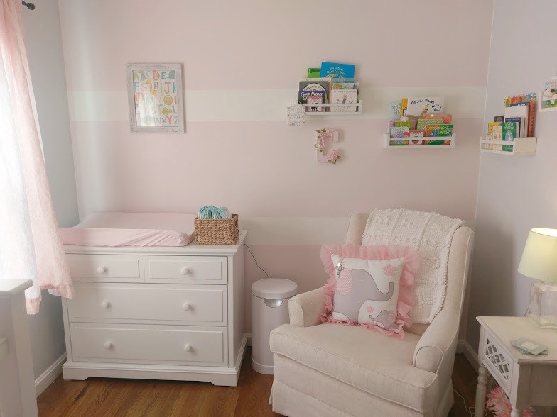 Pink baby girl nursery with changing table and rocking chair