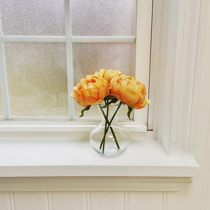 Peach peonies faux flowers on windowsill