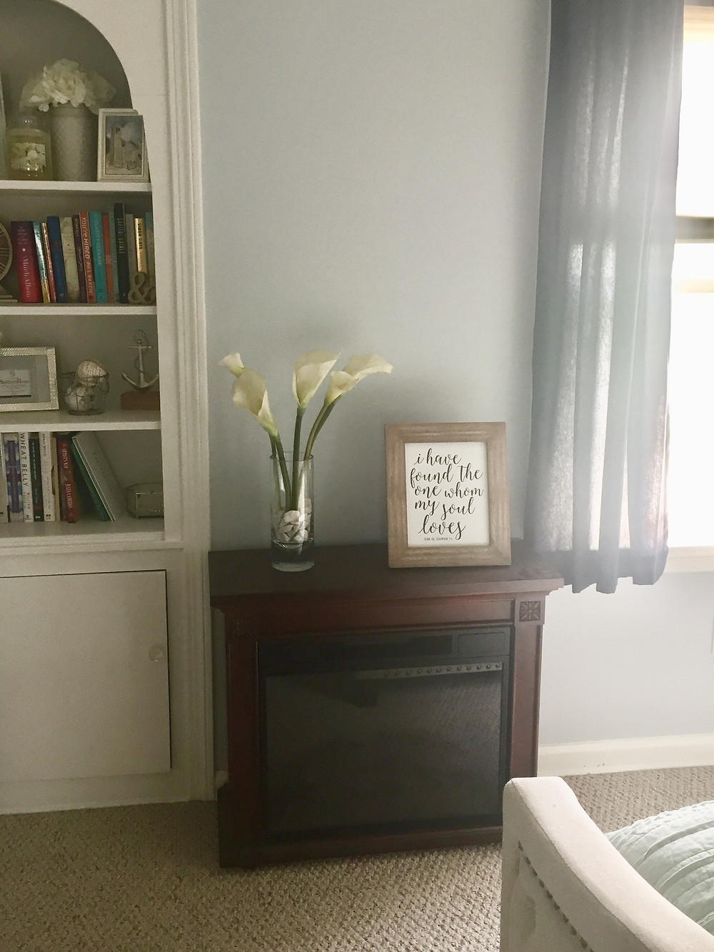 Bedroom fireplace with flowers and framed photo