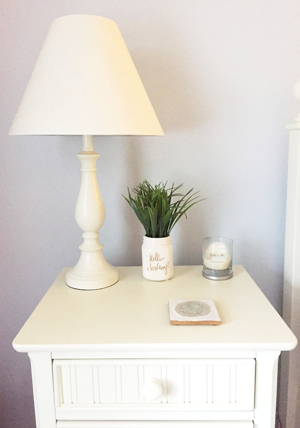 Potted grass in mason jar on white farmhouse nightstand