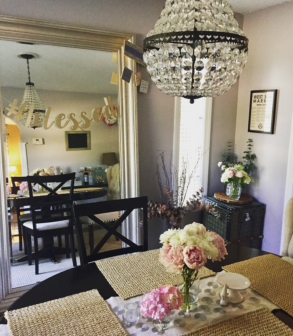 Gray dining room with chandelier and flowers