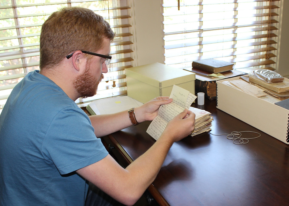 Cody working at Historic Sandusky- looking at a letter by Virginia Shearer Hopper