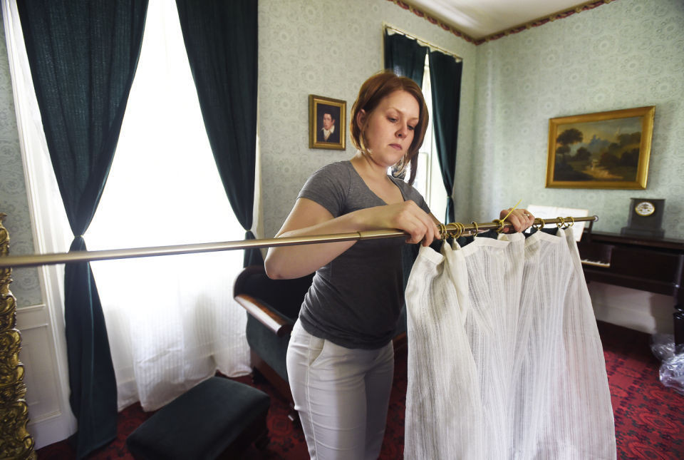 Brittney hangs a curtain in the Formal Parlor