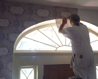 Bud Williams hanging the wallpaper in the formal entryway