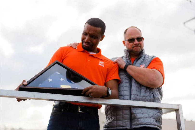 "From article, ""Jordan Jasper, assistant store manager at the Home Deport on Forest Lane in Dallas, receives a flag from Dave Rebtoy, Home Depot regional vice president on Thursday, Oct. 24, 2019.(SOHOSTORY - HOYOUNG LEE)"""
