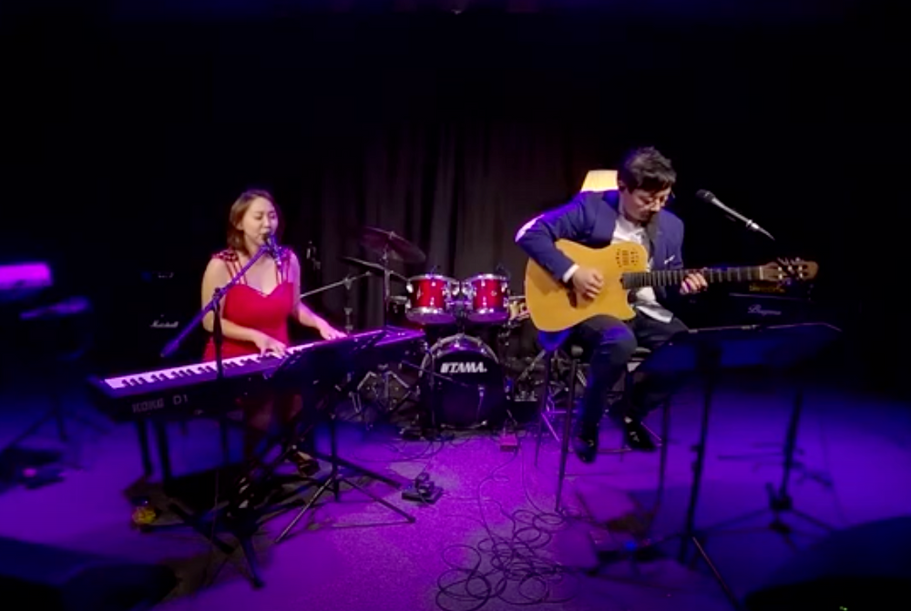 Ywenna performing with her guitarist and husband Kachi during Phase 2 at a studio.