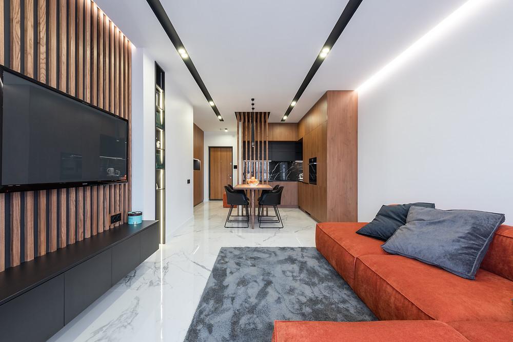Ambiente integrado - Sala de estar integrada com a sala de jantar e a cozinha, com elementos de madeira e uso de tons de cinza e vermelho para destaque