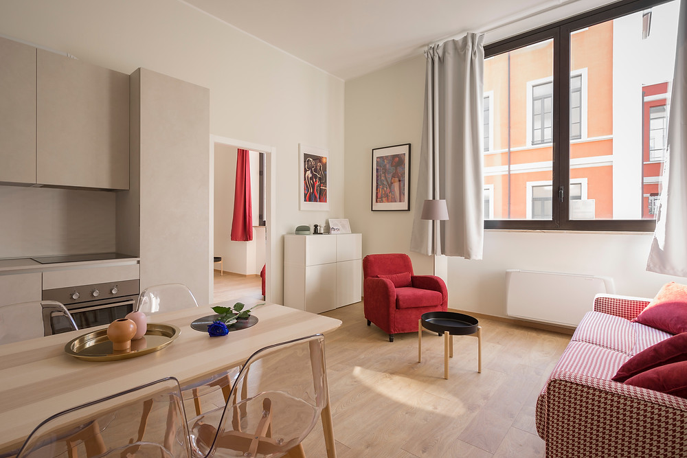 Ambiente integrado - Ligação da sala de estar e de jantar com a cozinha, utilizando tons claros em contraste com tons de vermelho