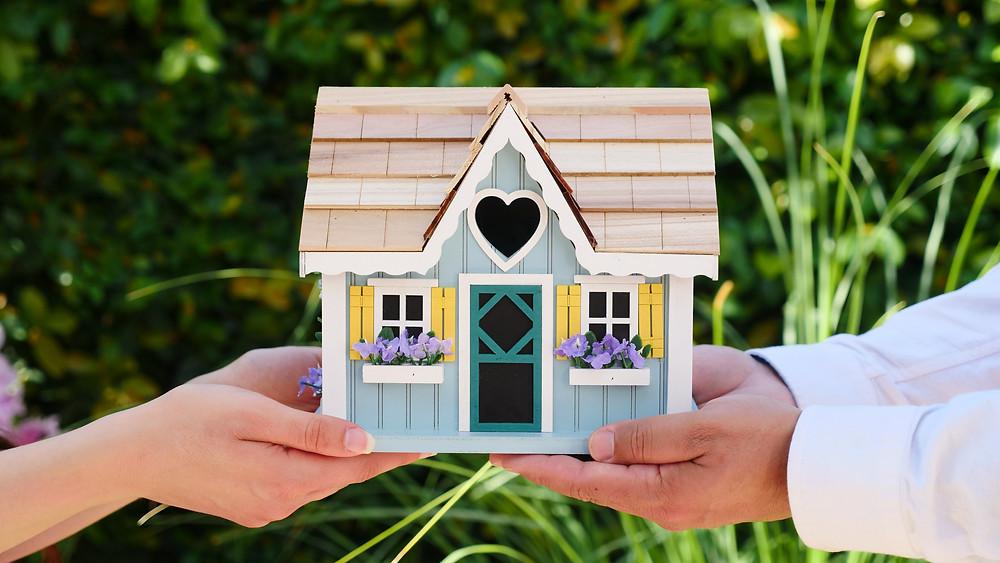 Imovel alugado - duas pessoas segurando a maquete de uma casa