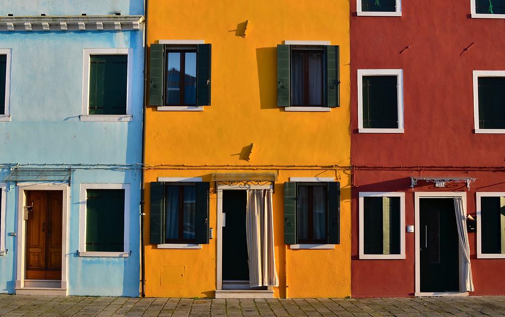 Decoração de cozinhas - Três prédios com diferentes cores (azul, amarelo e vermelho)