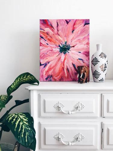 Cômoda branca com quadro de uma flor em cima, junto a um vaso.