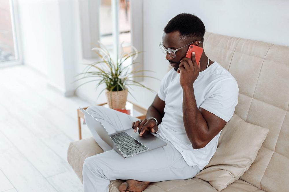 Homem mexendo no computador e falando ao celular enquanto está sentado no sofá