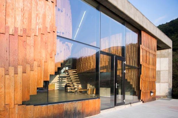 Iluminacao natural - Fachada de uma residencia com uso de madeira, vidro e concreto aparente, tendo uma grande entrada de luz pelas janelas