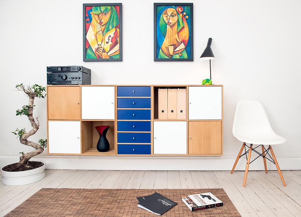 Design de interiores - Armário de madeira com tonalidade branca e azul com cadeira ao lado e quadros ao fundo