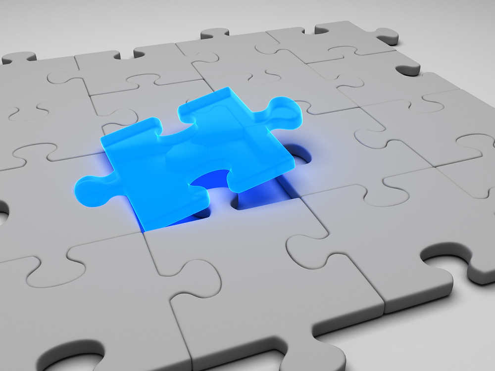 A grey jigsaw with a final blue piece being inserted