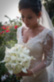 Bride looking at bouquet of roses