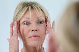 Senior woman looking at her skin in mirr