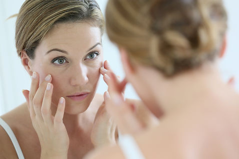 Middle-aged woman applying anti-aging cr