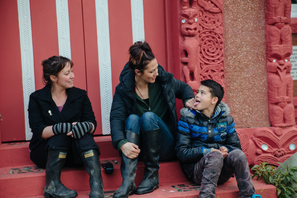 Kitty and Kirsten with tamaiti Joe, all three sitting on the steps of a wharenui.
