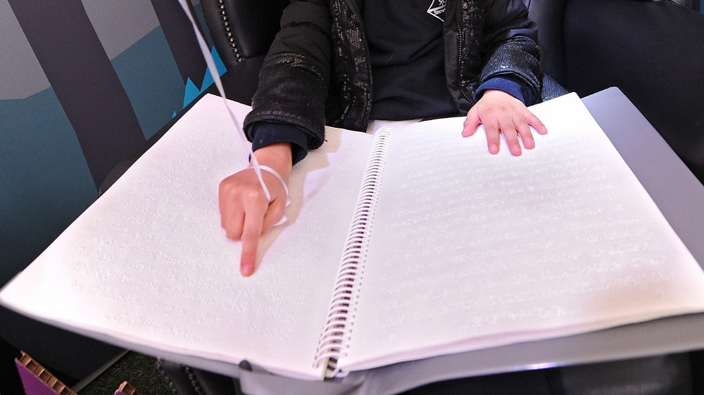 child's hands reading large braille book