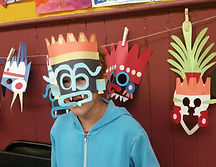 Witzilopoxtli - Un enfant portant une masque se tien devant plusieurs autre masques, A child in a mask stands in front of several other masks